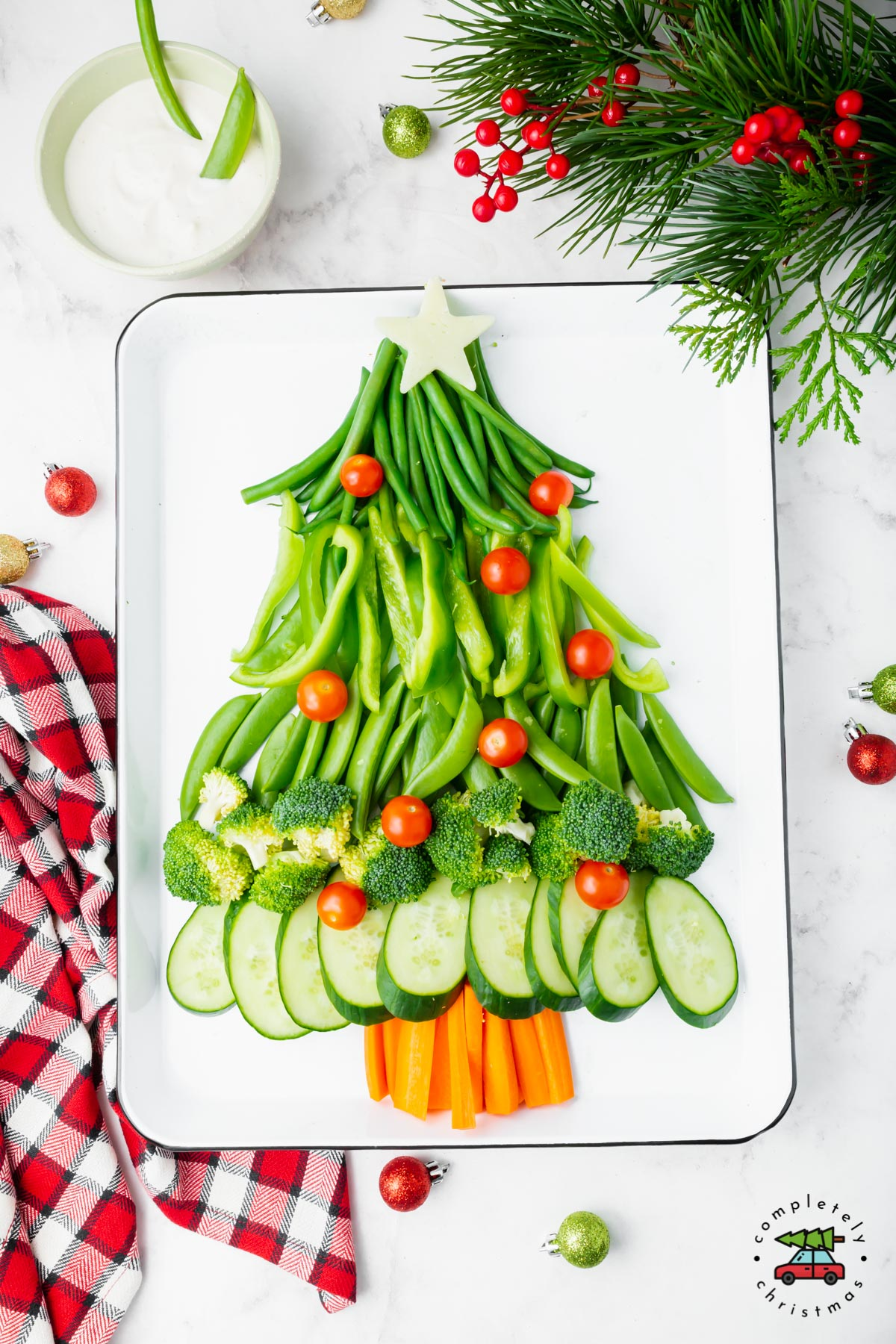 Vegetable platter in the shape of a Christmas tree on a white baking sheet.
